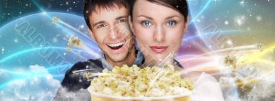 Portrait of young stylish modern couple watching movie against f