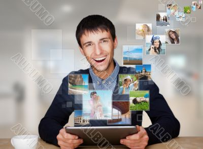 A technology man has images flying away from his modern tablet c