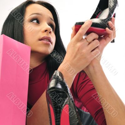 Beautiful European young woman shopping against white wall indoo