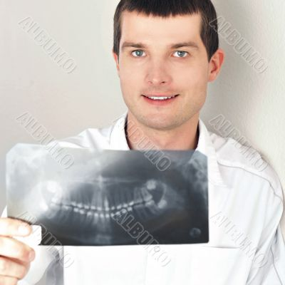 Portrait of smiling caucasian man doctor wearing uniform standin