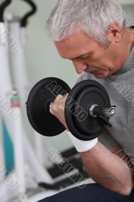 man lifting weight in sports room