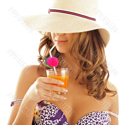 Woman drinking orange juice and wearing summer hat. Vacation con