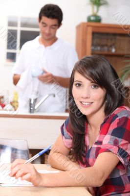 Young woman sitting at the kitchen table doing paperwork while her boyfriend washes the dishes