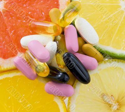 Group of pills on fruit slices ,orange, lemon, lime, grape fruit