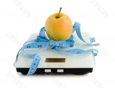 Apple on the scales measuring tape wrapped