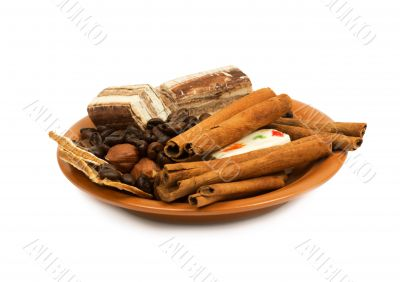 Sweets, cinnamon, nuts and coffee beans on a saucer.