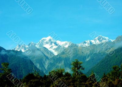 Mountains And Clouds Above Forests