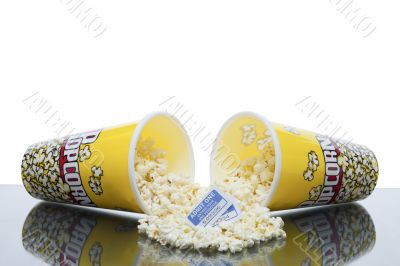 scattered popcorn from bucket with movie ticket