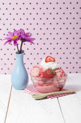 strawberry ice cream with napkin and spoon beside a flower base