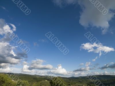 blue sky with grey clouds with tuscan landscape