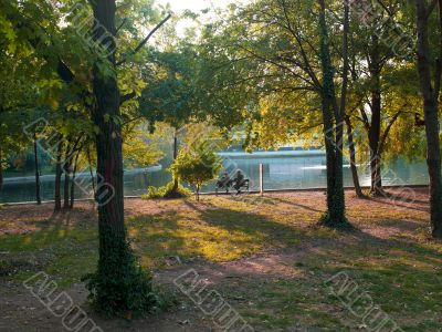 view of two people sitting on bench beside lake
