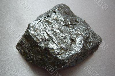 Silvery shiny stone on gray background.