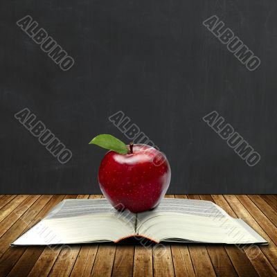 apple on a book with black board at the back