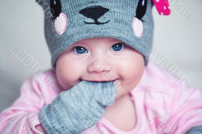 cute newborn baby girl in a funny hat and mittens