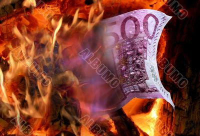 The wood fire burns a five hundred euro banknote