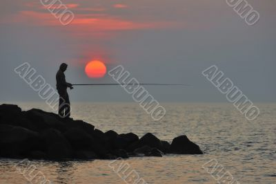 The fisherman at sunset is waiting for fish to bite