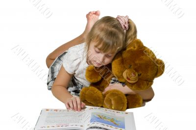 Beautiful little girl playing with a bear.