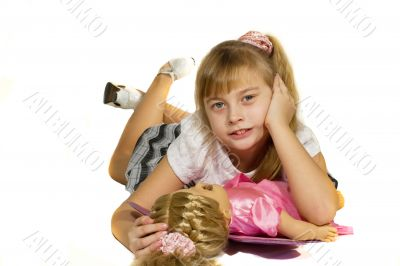 Beautiful little girl playing with a doll.