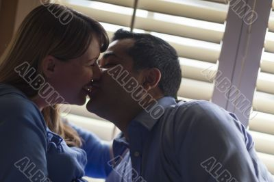 Mixed Race Couple Kissing Near the Light of the Window