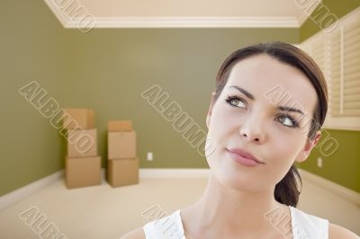 Contemplative Young Woman Daydreaming in Empty Room with Boxes