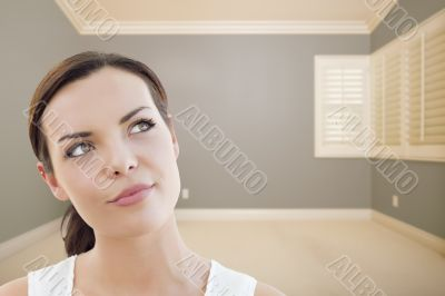 Young Woman Daydreaming in Empty Grey Room