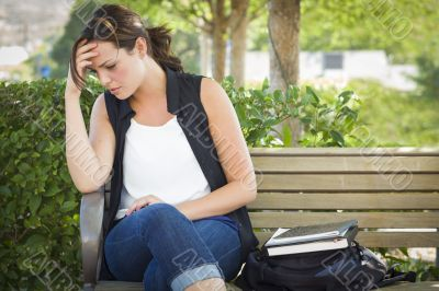 Upset Young Woman Sitting Alone on Bench Next to Books