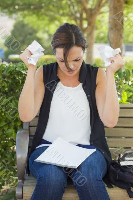 Upset Young Woman with Pencil and Crumpled Paper in Hands