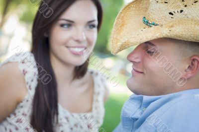 Mixed Race Romantic Couple with Cowboy Hat Flirting in Park
