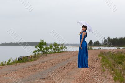 Beautiful girl in a blue dress with an umbrella