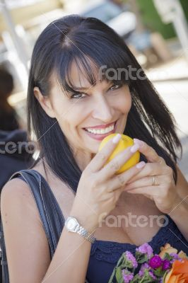Pretty Italian Woman Smelling Oranges at the Street Market