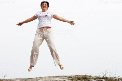 Adult smiling woman in white jumping outdoor