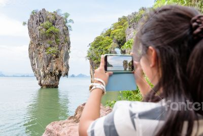 Female traveler shooting view by mobile phone