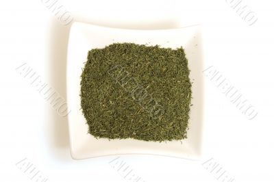 dried dill in square white bowl isolated