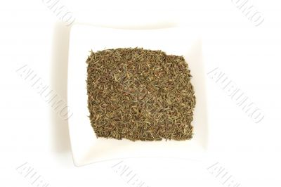 dried thyme in square white bowl isolated