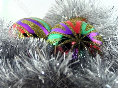 Two multi-coloured christmas spheres in a tinsel
