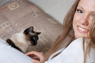 beautiful smiling girl in white with cat