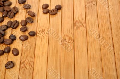 Grains of coffee on a carpet made of a bamboo