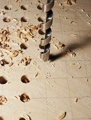 Drilling of apertures in a sheet of plywood