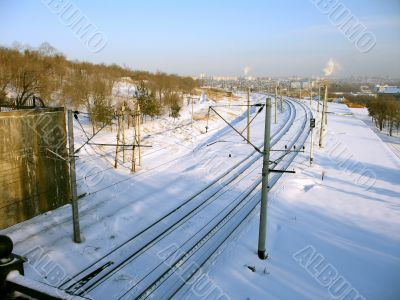 Railroad tracks covered by a snow near a hill