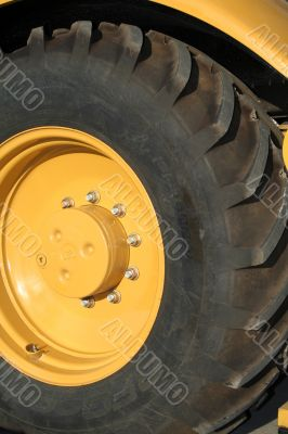 Wheel of a new yellow building tractor