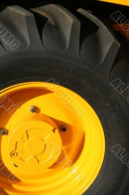 New wheel of a yellow building tractor