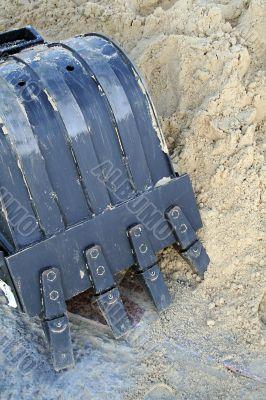 Black shovel bucket near to a heap of sand