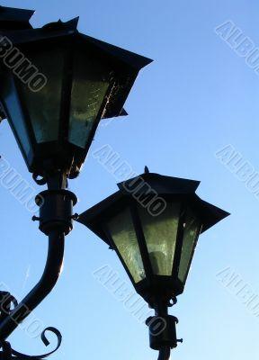 Old street lamp on blue sky background