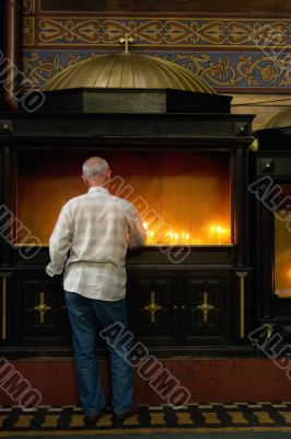 man with candle in churche