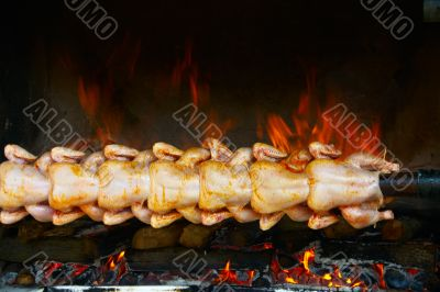 Broiling chicken on spit