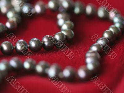 Black pearl necklace on red velvet2