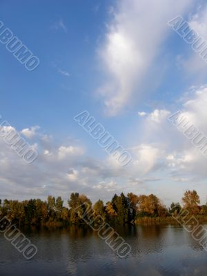 Summer sky. River bank with trees