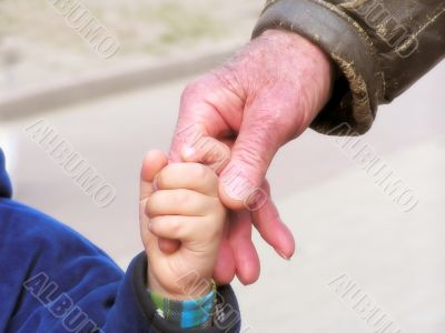 The kid holds a hand of the grandfather
