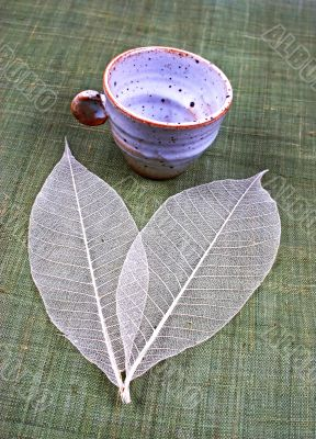 Pottery cup and leaves