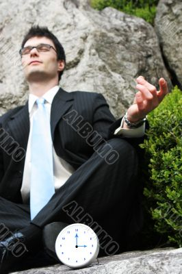 Businessman meditating outside.